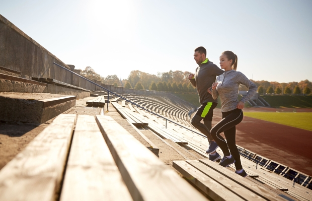 61982730 - fitness, sport, exercising and lifestyle concept - happy couple running upstairs on stadium