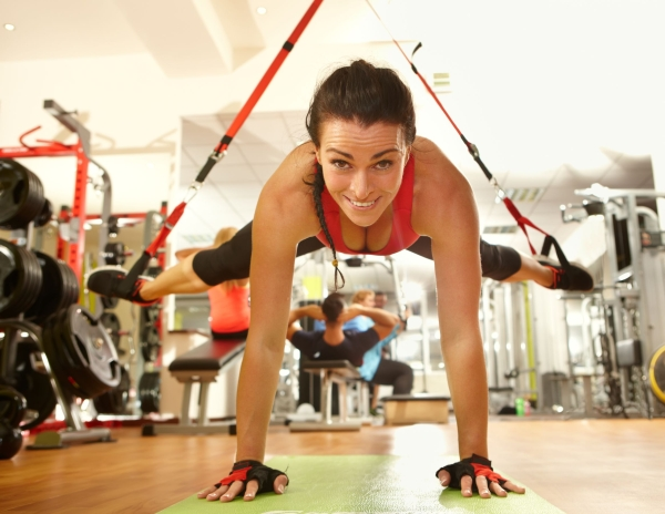 36305704 - happy woman enjoying hard trx suspension training in gym.