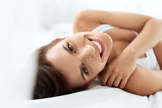 60242633 - woman's health. closeup portrait of beautiful smiling woman with fresh face, soft skin having fun lying on white bed. healthy happy girl with natural makeup relaxing indoors. beauty, skin care concept