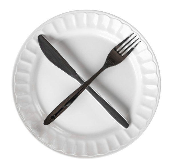 73467810 - intermittent fasting concept with knife and fork showing cross symbol on white plate, isolated on white