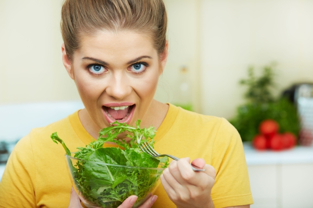 101226629 - happy woman eating  vegetarian food,  standing against  home kitchen interior background. yellow color clothes. woman face close up portrait.