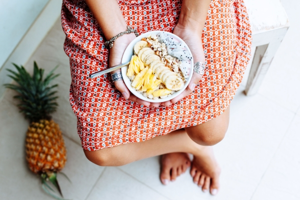 73426470 - girl holdingin hands smoothie bowl with mixed tropical fresh fruits, top view from above. summer healthy diet, vegan breakfast.