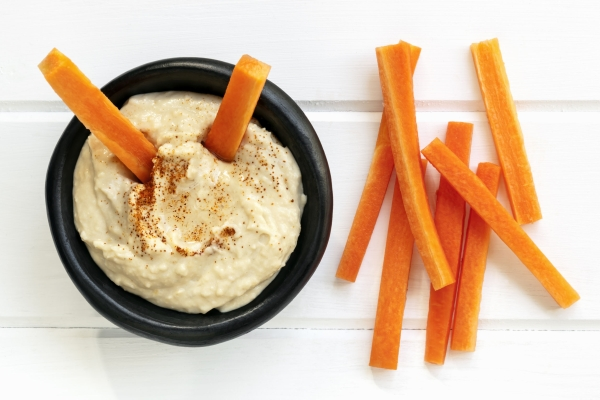63020667 - hummus with carrot sticks.  top view over white timber.