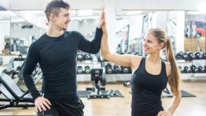 Sporty fitness couple giving high five to each other in gym.