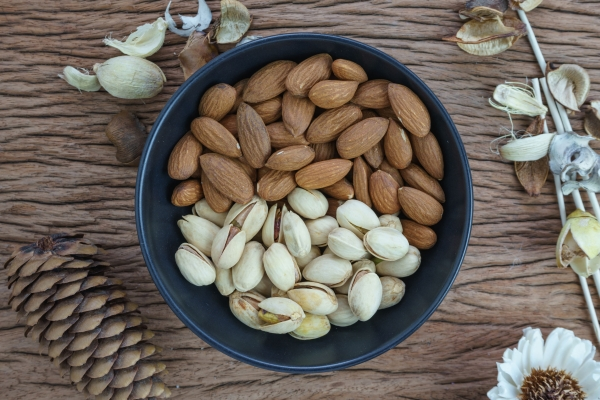 78006524 - roasted healthy delicious pistachios and almonds nuts food in black bowl on wooden table background.