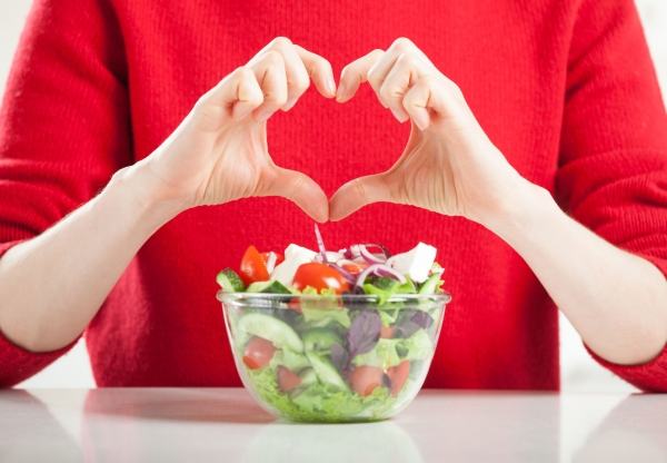 86642281 - healthy food for healthy life! unrecognizable woman showing heart sign over the salad made from fresh vegetables; healthy eating concept