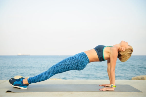 84868437 - young athletic woman exercising outdoors: reversed plank for total body strength