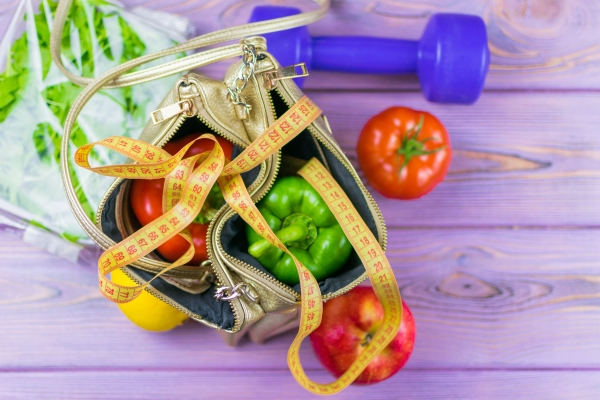 101787666 - female weight loss. diet. a set of vegetables in a woman's handbag. a funny concept is the decision of a woman to lose weight.