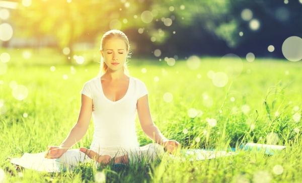 60130869 - young woman enjoying meditation and yoga on green grass in the summer on nature