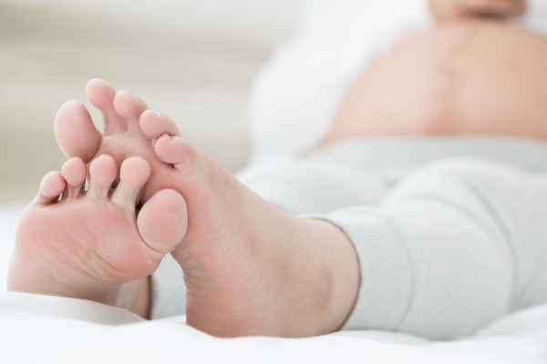 81482375 - southeast asian pregnant women with swelling feet, pain foot and lying on bed in the room. swollen feet and fetal poisoning or toxicity concept