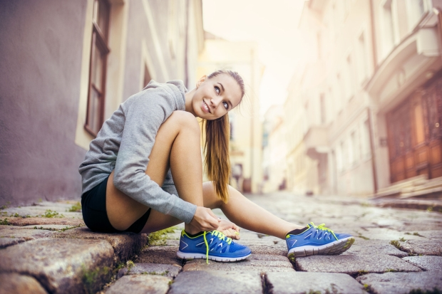 33161014 - young female runner is tying her running shoes on tiled pavement in old city center
