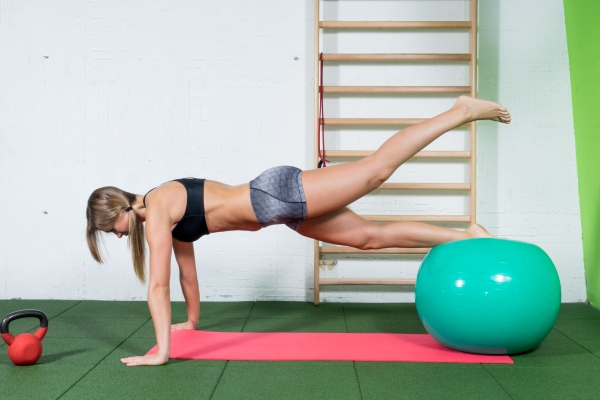 87170695 - young girl doing pilates exercises with fitness ball