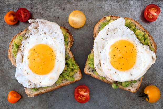 43849735 - open avocado, egg sandwiches on whole grain bread with tri-colored tomatoes on rustic baking tray