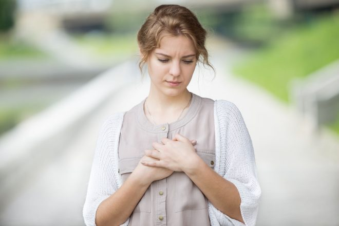 58685361 - portrait of stressed beautiful woman walking on the street and touching her chest with sad expression or having heart ache. attractive model suffering from pain outdoors in summer park