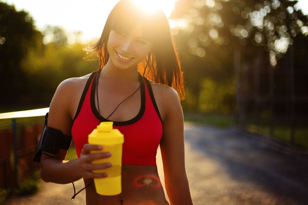 64748524 - young sport woman posing in fitness outfit with protein shake