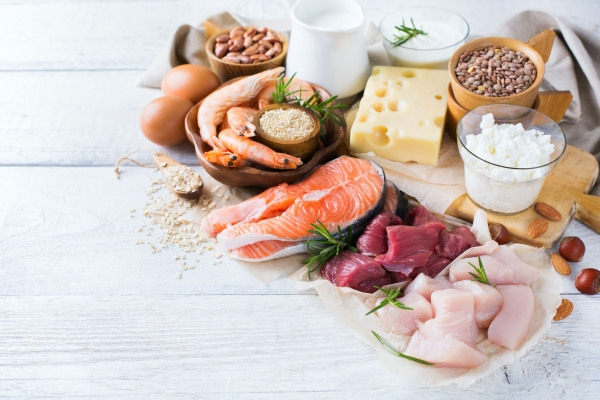 74070854 - assortment of healthy protein source and body building food. meat beef salmon shrimp chicken eggs dairy products milk cheese yogurt beans quinoa nuts oat meal. copy space background