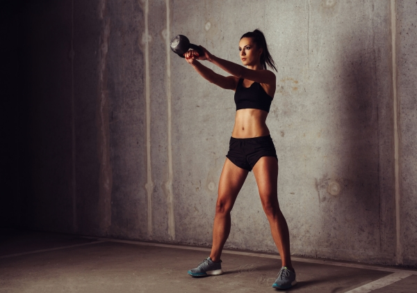 65949435 - brunette sportswoman working out her arms with a kettlebell