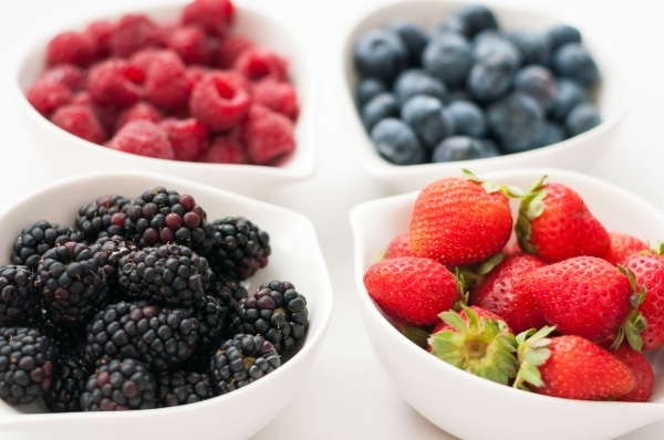 65275231 - on a white background in white bowls of fresh, juicy wild berries blueberries raspberries strawberries and blackberries, delicious supplement to any diet meals.