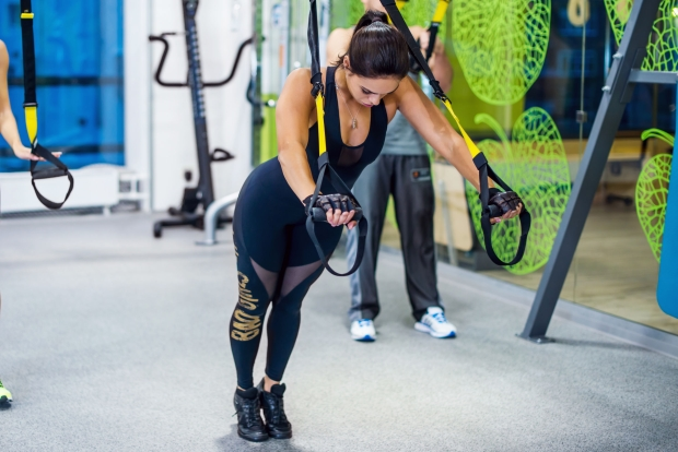 48565578 - young woman training exercise push ups with trx fitness straps in the gym  concept sport workout healthy lifestyle.