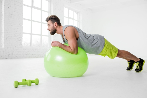 71779129 - man exercising with fitball