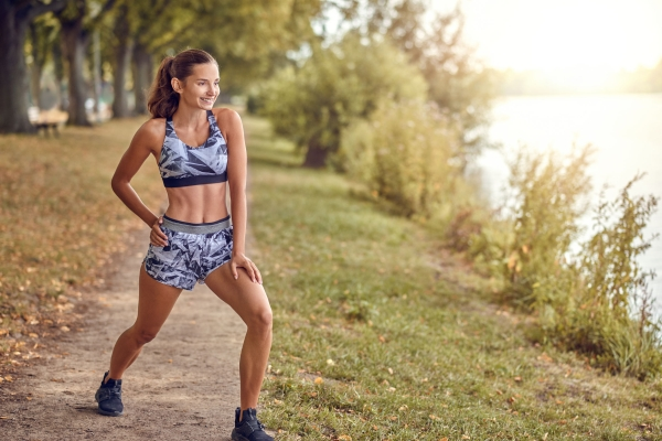 104978745 - fit muscular woman working out in a park on a footpath alongside a peaceful lake or river doing stretching exercises in a health and fitness concept