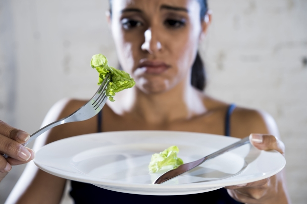 70977624 - young woman or teen girl holding dish with ridiculous little lettuce as her food symbol of crazy diet in nutrition disorder concept anorexia and bulimia and refusing to eat in diet calories obsession