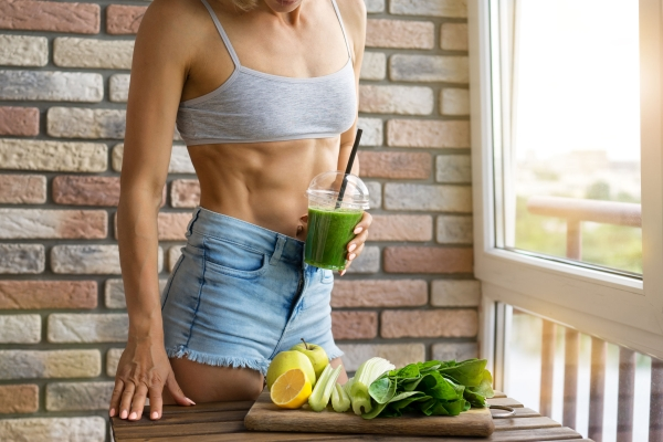 103659011 - fit woman drinking vegetable green detox smoothie. raw food diet