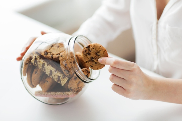 57615815 - people, junk food, culinary, baking and unhealthy eating concept - close up of hands with chocolate oatmeal cookies and muesli bars in glass jar