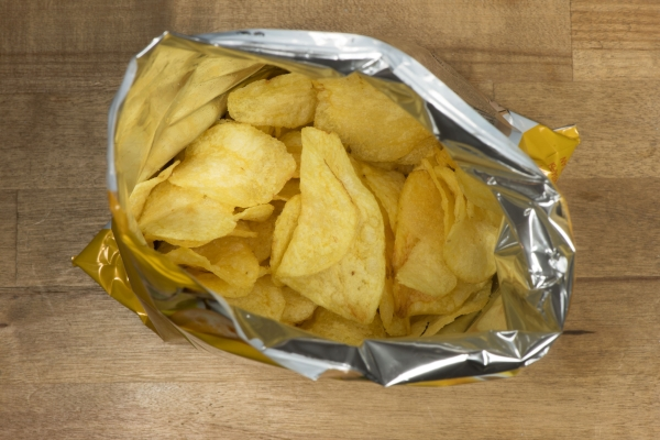 38984632 - potato chips in an open bag on a wooden table