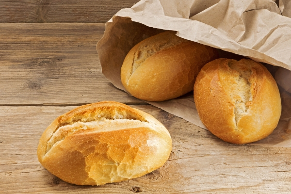 35375797 - bread rolls in a paper bag on a rustic wooden table, fresh from the bakery for breakfast