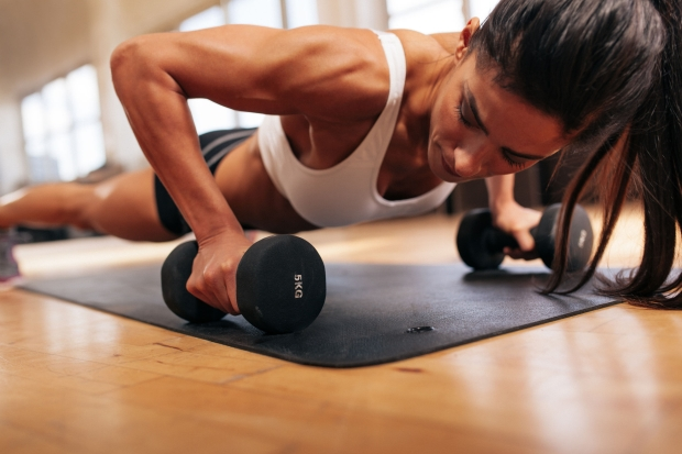 43852621 - strong young woman doing push ups exercise with dumbbells. fitness model doing intense training in the gym.