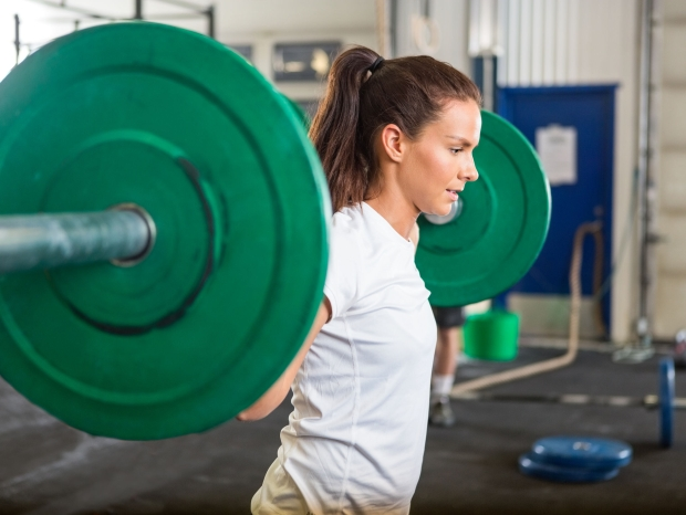 35442625 - fit woman lifting barbell in gym