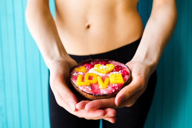 101342551 - concept of diet, proper nutrition and health. slim woman holding smoothie bowl on a turquoise background