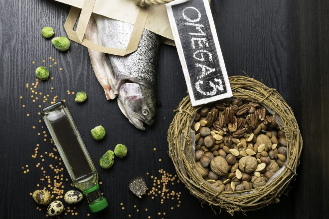 101227408 - healthy fat salmon or trout, oil, nuts. omega 3 source, seeds, chia, lentils,brussels sprouts, eggs on dark wood background