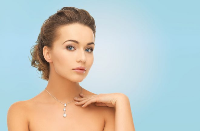 35172329 - beauty, people and jewelry concept - woman wearing shiny diamond pendant over blue background