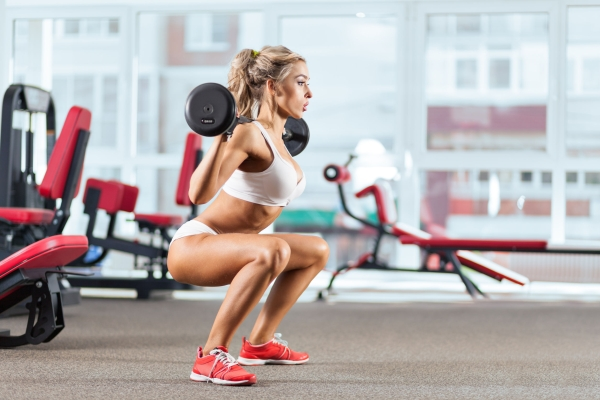 40338269 - sportive woman doing squatting with a barbell in the gym