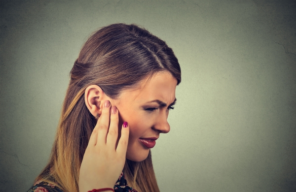 55040347 - tinnitus. closeup side profile sick young woman having ear pain touching her painful head isolated on gray background