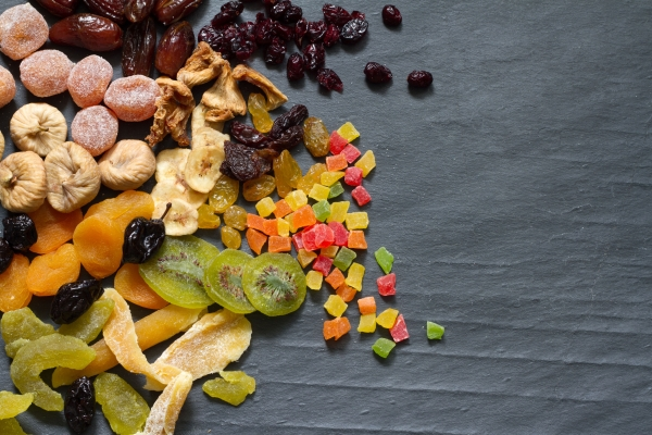 49746184 - candied dried mixed assortment of exotic fruits on black marble