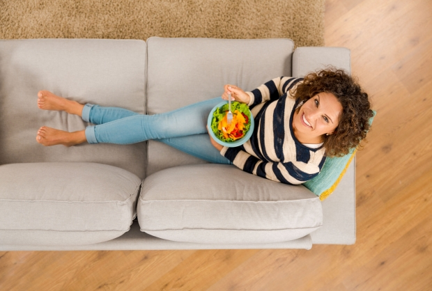 71963468 - top view of a beautiful woman on the sofa eating a healthy salade
