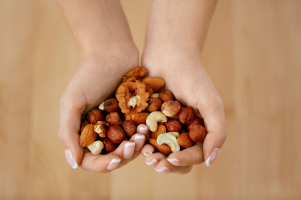 96824144 - nuts heart. hands holding different nuts