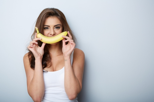 35974062 - a woman making fun with a banana