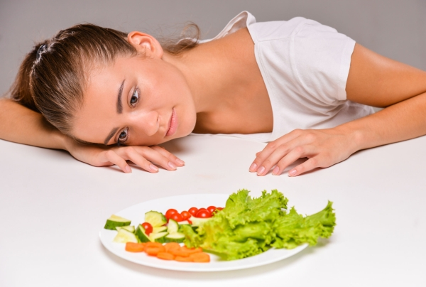 44132464 - young sad woman with a plate of salad.