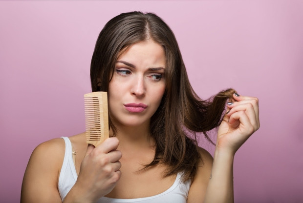 64012896 - woman brushing her hair with a wooden comb