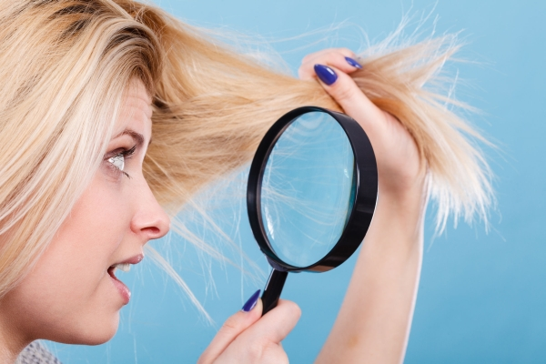77196297 - haircare and hairstyling, bad effects of bleaching concept. blonde woman looking at her damaged, split hair ends through magnifying glass.