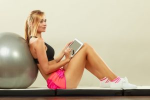 79549864 - fitness woman blonde fit girl sitting on floor and looking into tablet pc