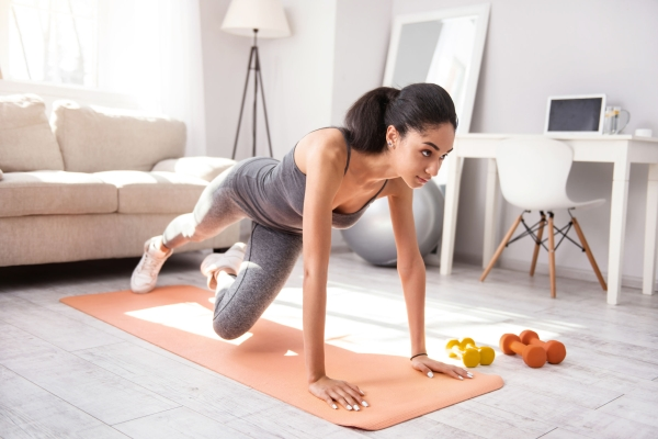 100079783 - advanced exercise. charming dark-haired woman doing a plank and alternating her legs while exercising in the morning