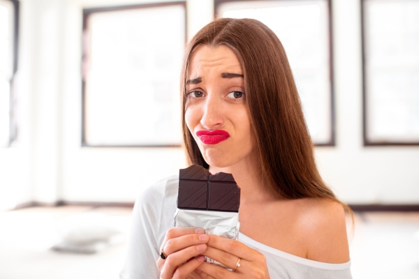 52148610 - woman with disappointed emotions thinking about sweet food worrying about calories and weight sitting in the sport gym