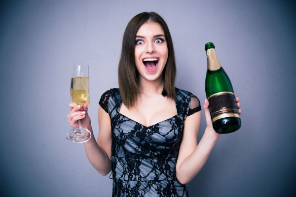 38430940 - happiness woman holding two glass and bottle of champagne over gray background. wearing in dress. looking at camera