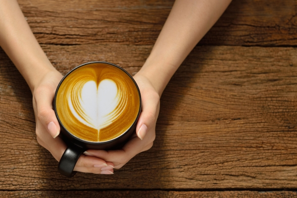 52650358 - woman holding cup of coffee latte, with heart shape