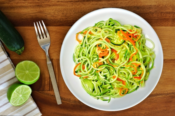 52586120 - healthy zucchini noodle dish with carrots and lime on wood background, overhead view
